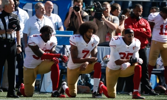 SEATTLE, WA - SEPTEMBER 25: Colin Kaepernick #7 and members of the San Francisco 49ers kneel during the national anthem prior to the game against the Seattle Seahawks at CenturyLink Field on September 25, 2016 in Seattle, Washington. (Photo by Otto Greule Jr/Getty Images)